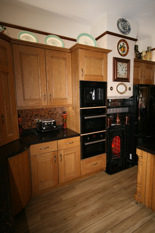 Dark Staron Worktops With Stained Oak Doors